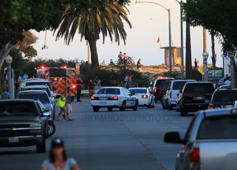 From the street at sunset 7/6/14: a somewhat familiar scene of emergency and police vehicles congregating at Wedge as the red flag on the guard stand is barely affected by a gentle breeze.